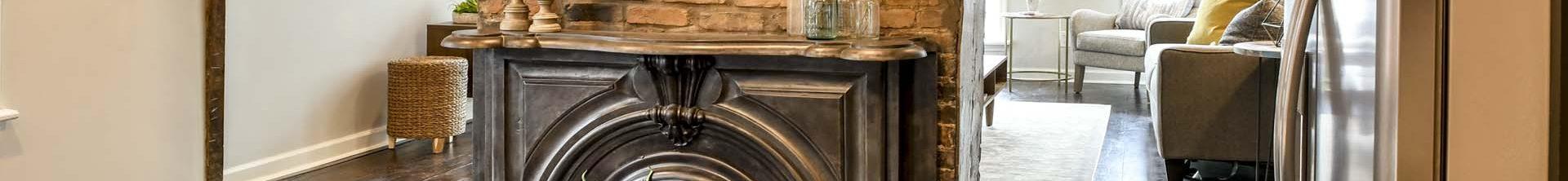 Louisville Home Staging, Louisville Interior Design, Louisville Renovation Design, Louisville Kitchen Design, Black Kitchen Cabinetry, Stainless vent hood, reclaimed hardwood flooring, artwork, accessories, kitchen island, granite countertops, stainless appliances, gas range, kitchen fireplace, brick fireplace