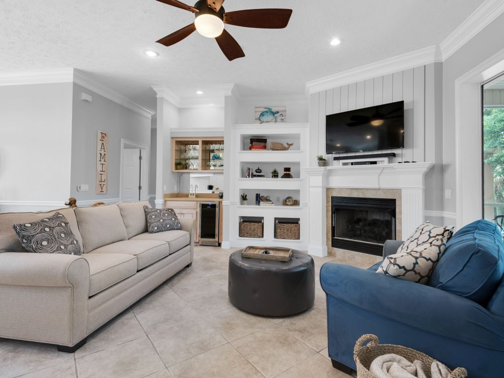 Weekend getaway, Winter Getaway, Louisville interior designer, seaside retreat, vacation home, beach home, ceramic tile floor, wainscoting, fireplace mantel, bookshelves, blue fabric chair, tan sofa, round leather ottoman, wet bar