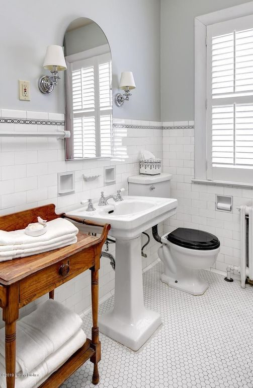 white tile bathroom, plantation shutters, penny tile floor, pedestal sink, chrome fixtures, antique table