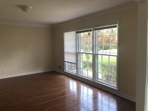 empty living room; red oak floors, wide window cream wall paint; 8-ft ceiling