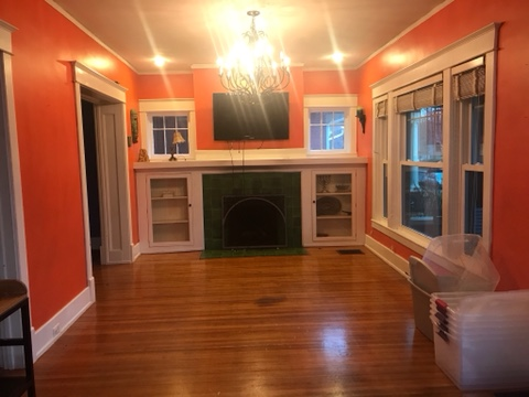 fireplace, white cabinets, hardwood floors, empty dining room, empty living room