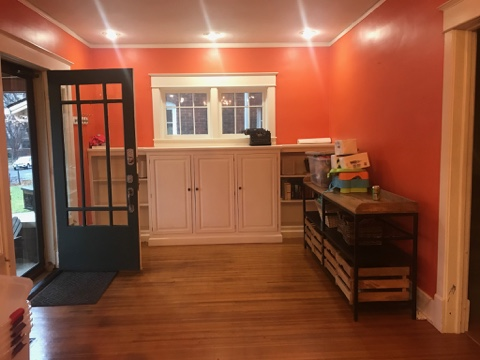 orange wall paint, storage unit in entry way, white cabinets